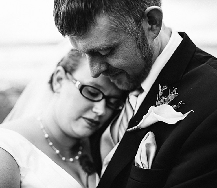 Black and white of bride and groom embracing each other at their Seattle beach side wedding